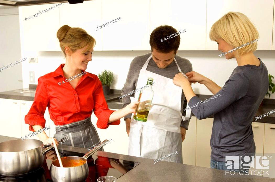 Stock Photo: Two young women helping a young man in wearing an apron in the kitchen.
