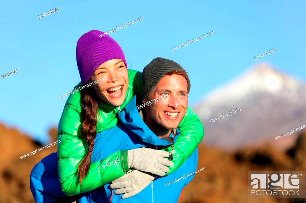 Stock Photo: Couple piggyback happy in active lifestyle having fun on hike. Fresh young joyful interracial couple. Asian woman hiker and Caucasian man in outdoor activity on.