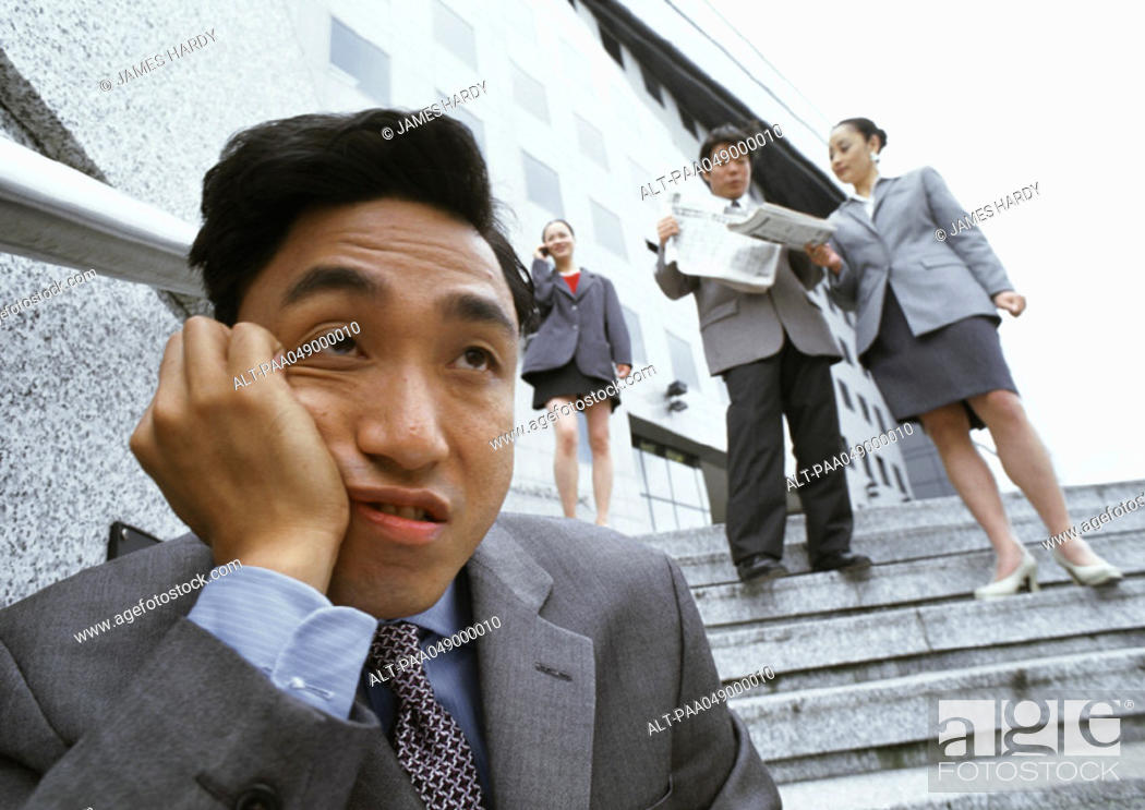 Stock Photo: Man sitting on stairs, hand on cheek, people in background.