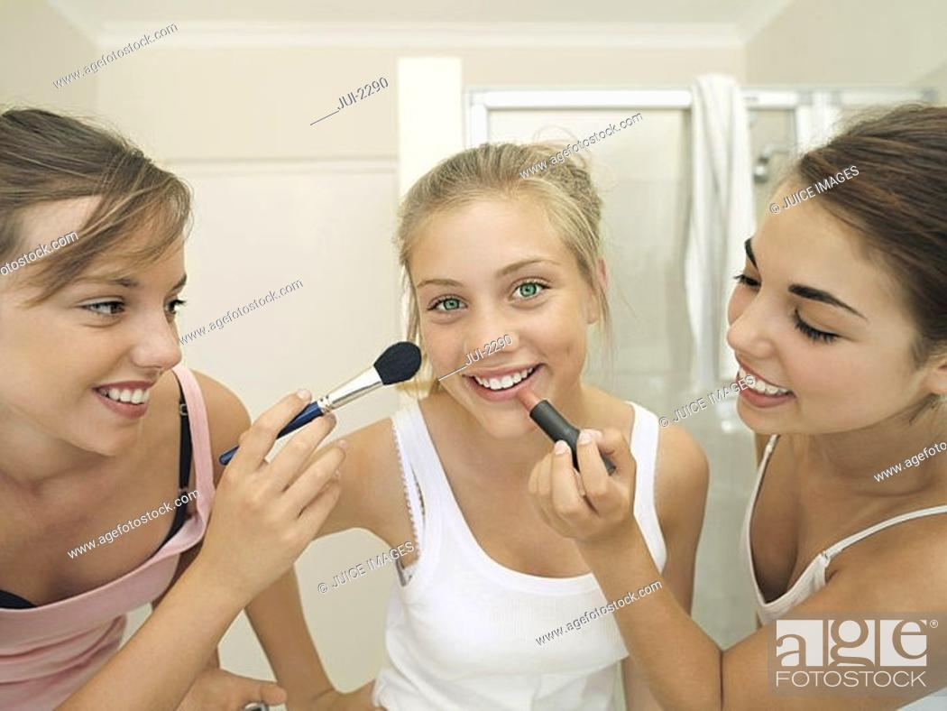 Stock Photo: Teenage girls 15-17 applying make-up to friend's face, smiling, close-up.