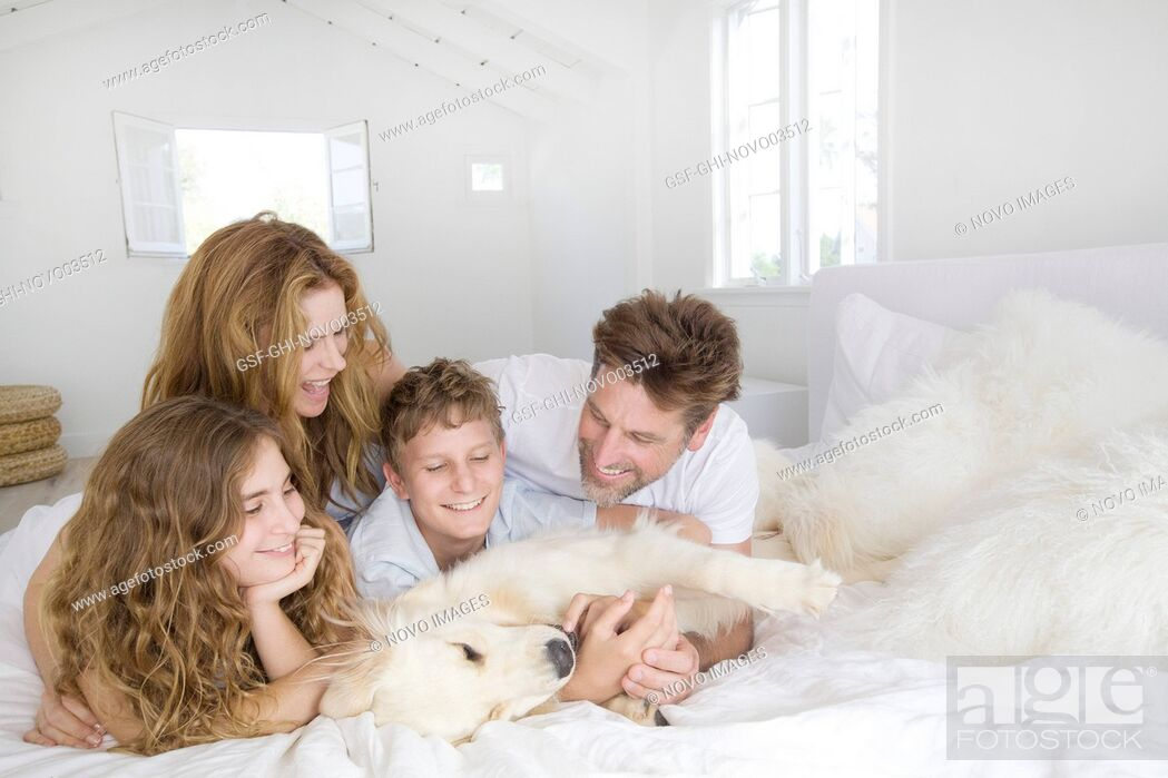 Imagen: Happy Family Laying on Bed with Pet Dog.