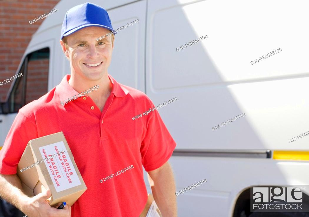 Stock Photo: Delivery man holding cardboard box.