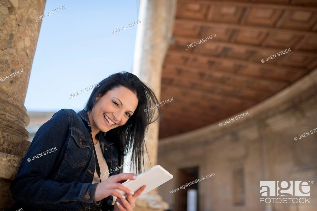 Stock Photo: Spain, Granada, happy young woman with tablet at the Alhambra.