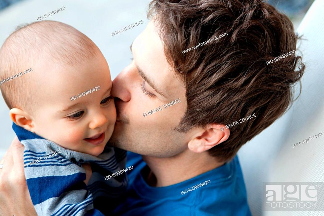 Stock Photo: Father kissing baby son on cheek.