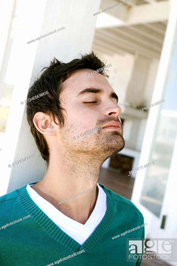 Stock Photo: Portrait of a young man with eyes closed, leaning against terrace beam.