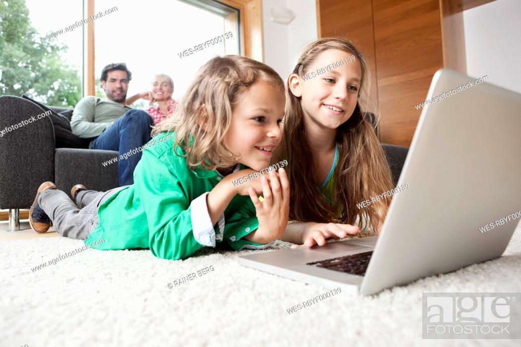Stock Photo: Germany, Bavaria, Nuremberg, Girl and boy using laptop in living room.