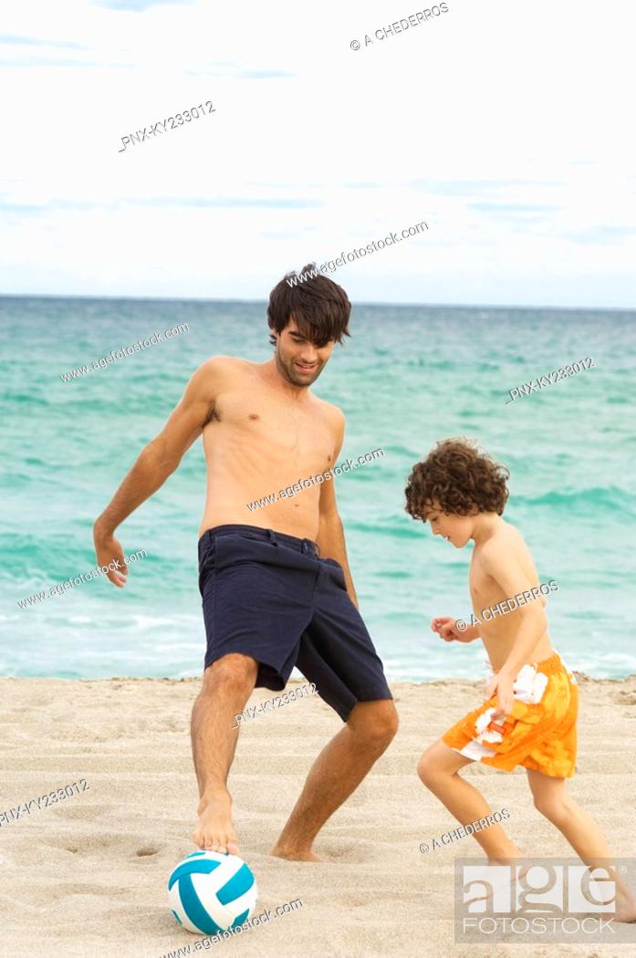 Stock Photo: Boy playing soccer with his father on the beach.