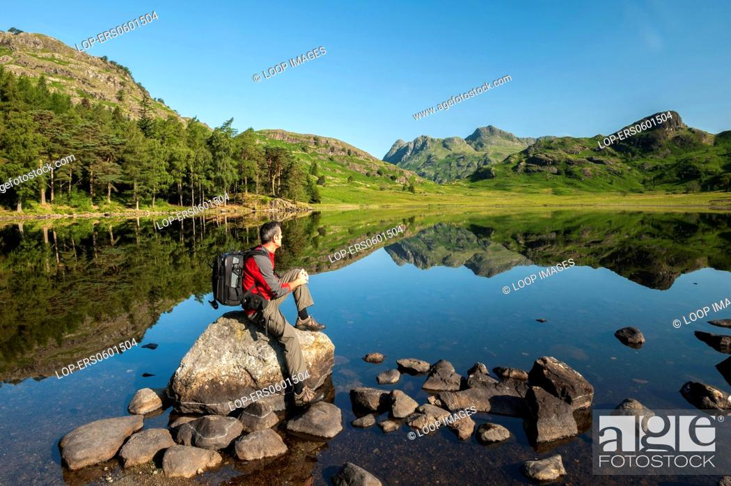 Stock Photo: A walker at Blea Tarn and The Langdale Pikes.