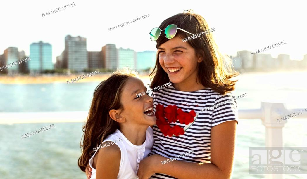 Stock Photo: Two happy girls on the beach at sunset.