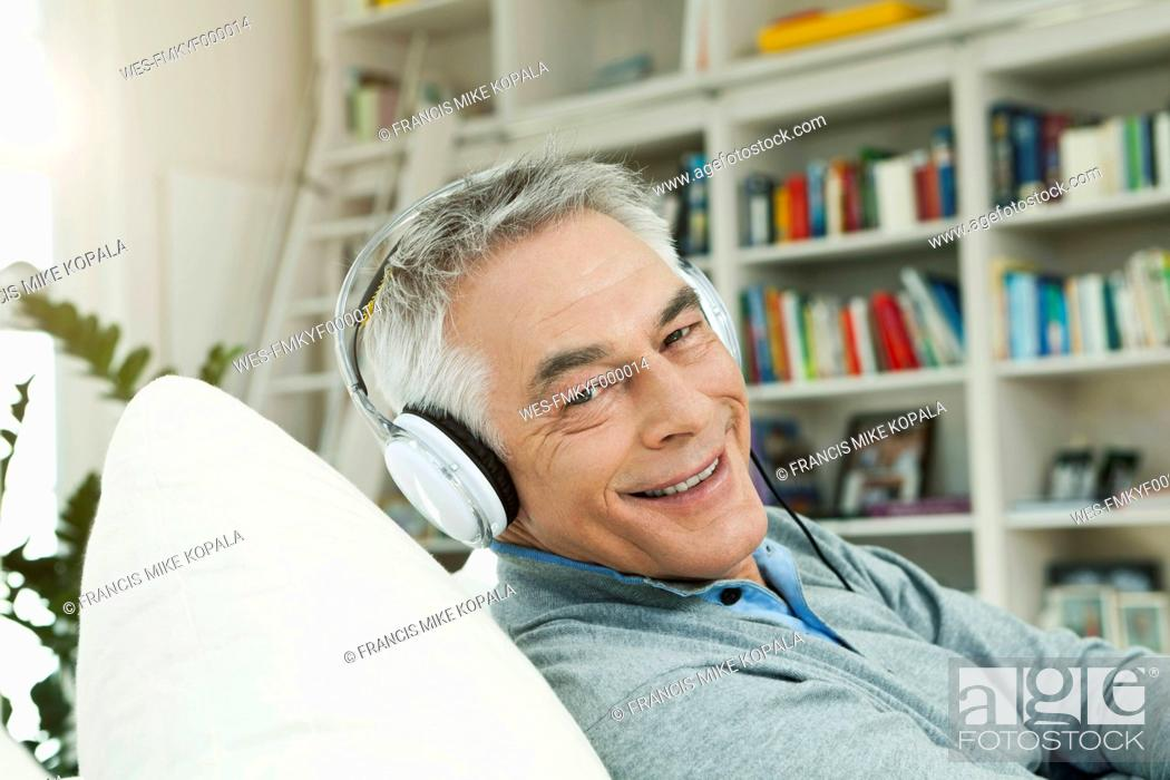Stock Photo: Germany, Berlin, Senior man with head phones on couch, portrait.