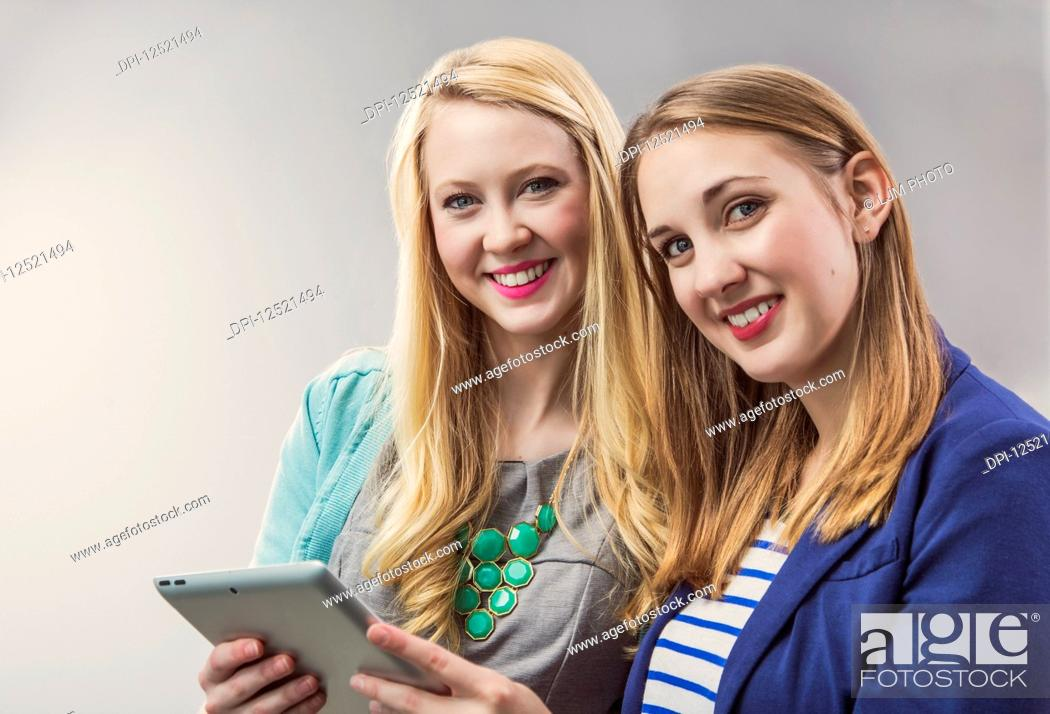 Stock Photo: Two beautiful young women who are millennial business professionals working together using a tablet and posing for the camera at their workplace; Sherwood Park.