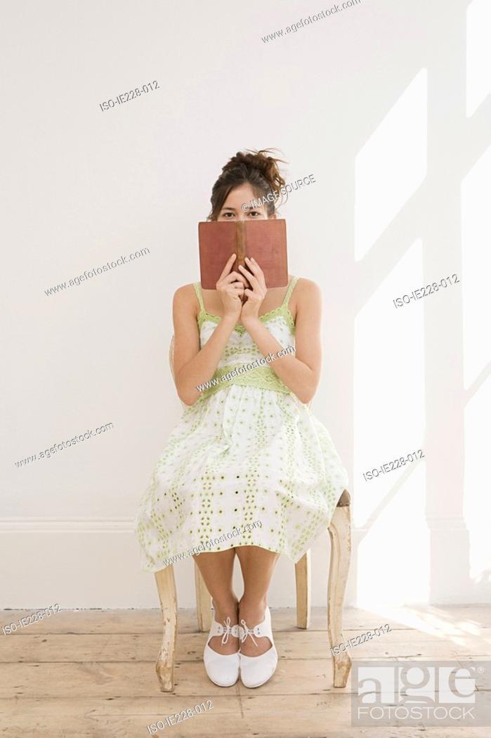 Stock Photo: Woman hiding behind a book.