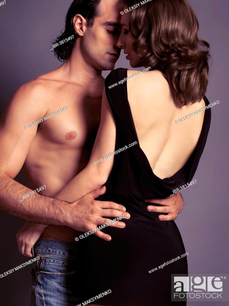 Stock Photo: Man with bare torso and woman in black dress about to kiss.