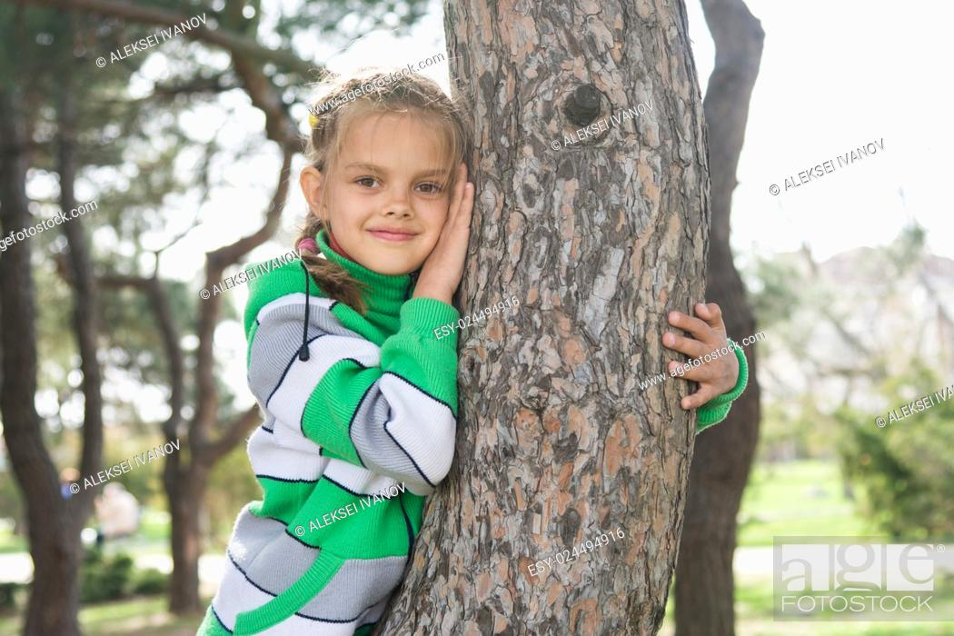 Photo de stock: Joyful seven-year old girl sitting on a tree trunk in the early spring.