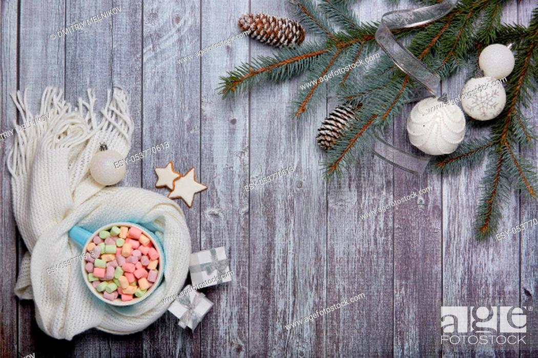 Stock Photo: Mug of cocoa with marshmallow, woolen white scarf, gift boxes, fir tree branches and Christmas ornaments on grey wooden background.