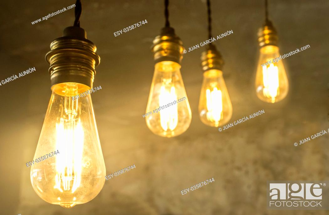 Imagen: Four hanging light bulbs over oxide dark color concrete background. Closeup.