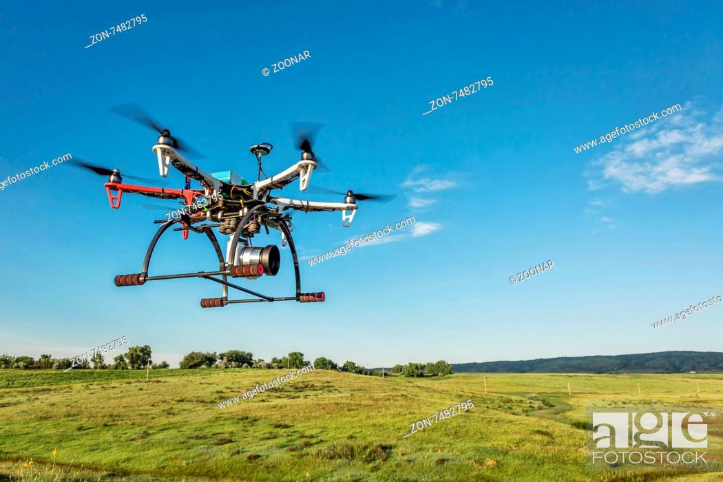 Stock Photo: FORT COLLINS, CO, USA, June 28, 2015: DJI F550 Flame Wheel hexacopter drone with Sony A6000 camera flying over foothills prairie,.