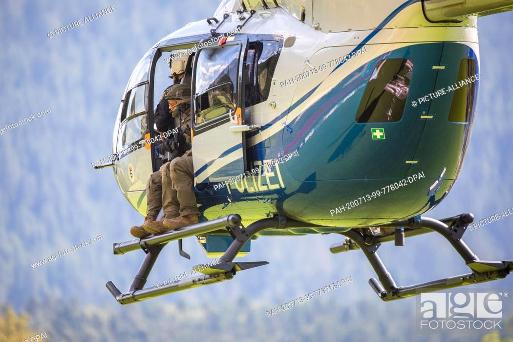 Stock Photo: 13 July 2020, Baden-Wuerttemberg, Oppenau: A police helicopter with special forces on board takes off from a sports field.