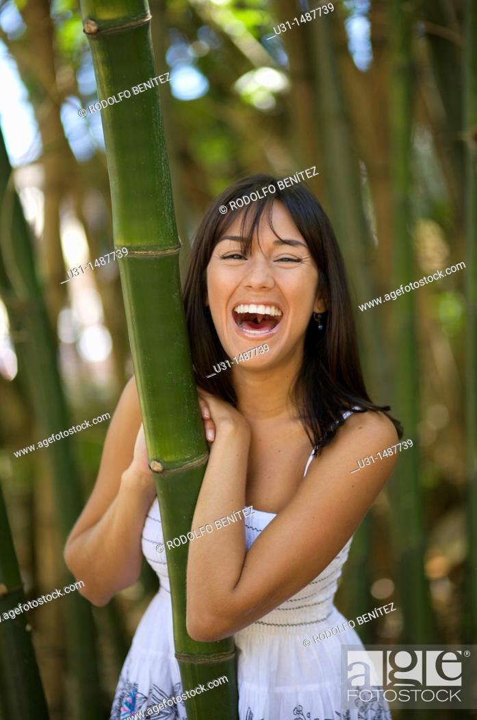 Stock Photo: Latin woman in bamboo forest smiling at camera.