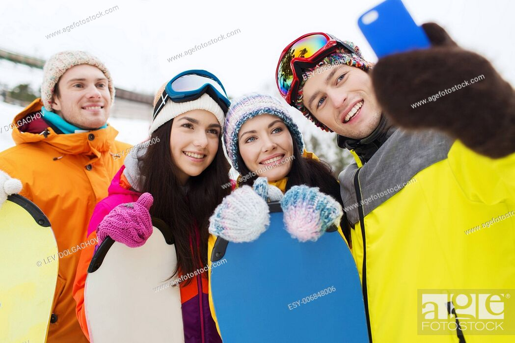 Stock Photo: winter sport, leisure, friendship, technology and people concept - happy friends with snowboards and smartphone taking selfie.