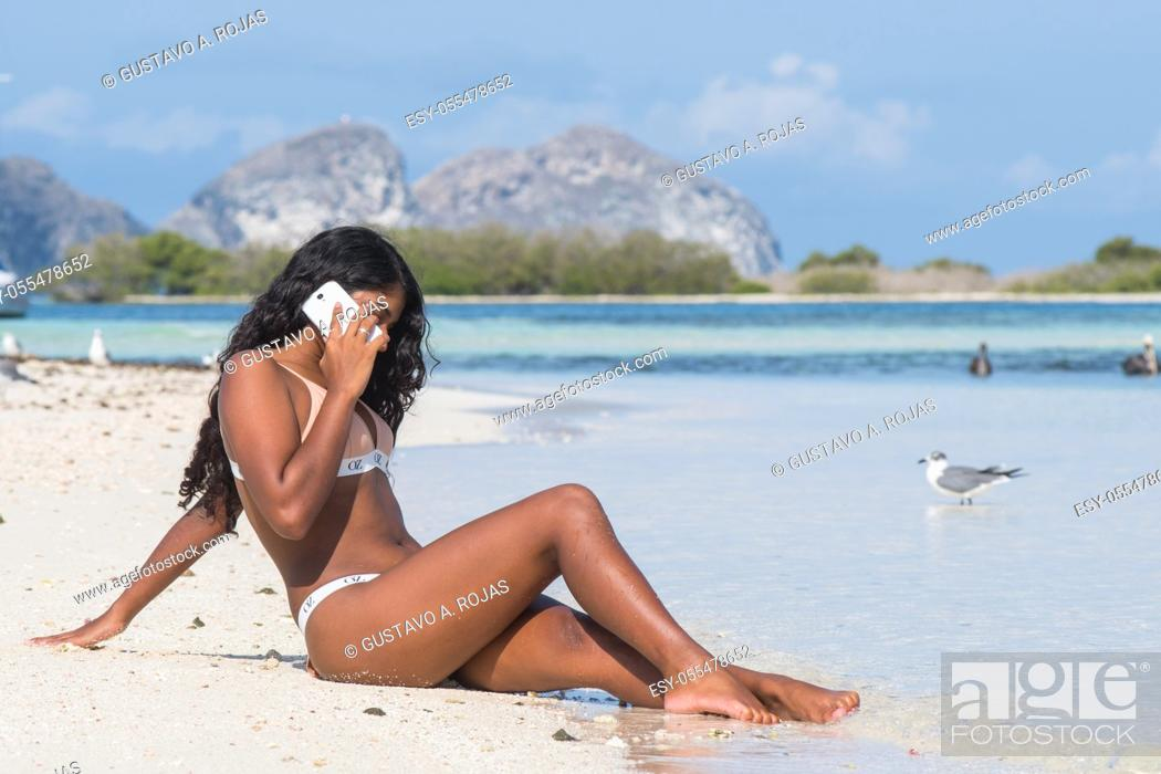 Stock Photo: Beautiful young woman talking on the mobile phone in the tropical beach.