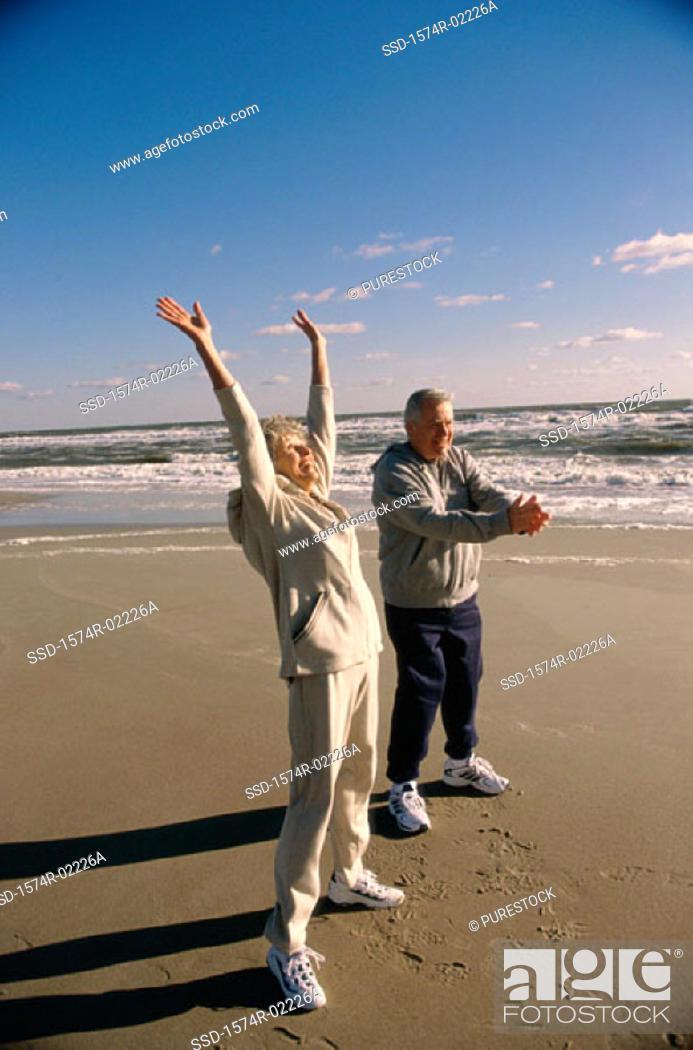 Stock Photo: Side profile of a senior couple exercising on the beach.