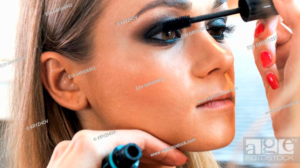 Photo de stock: Macro of makeup artist painting model's eyes with mascara.