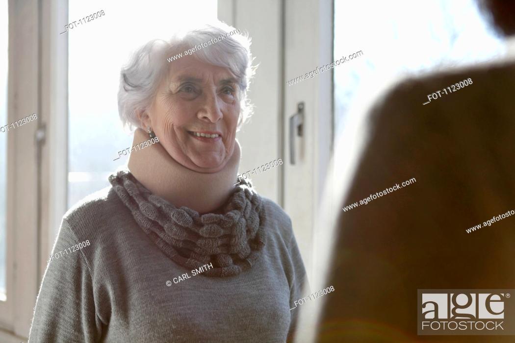 Stock Photo: A smiling senior woman wearing a neck brace.