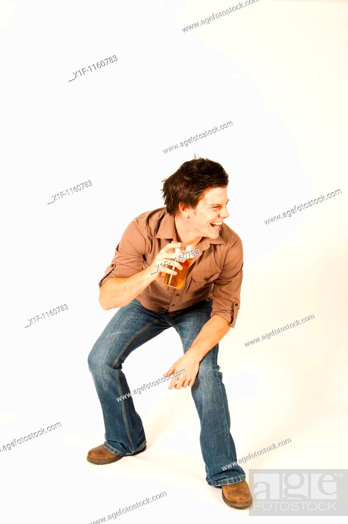 Stock Photo: Happy young man drinking a pint of beer lager.