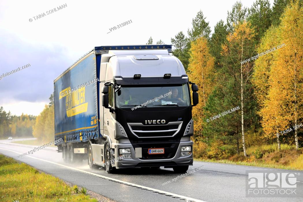 Stock Photo: Raasepori, Finland - October 7, 2017: New Iveco Stralis XP truck pulls trailer along wet highway on rainy day of autumn in South of Finland.