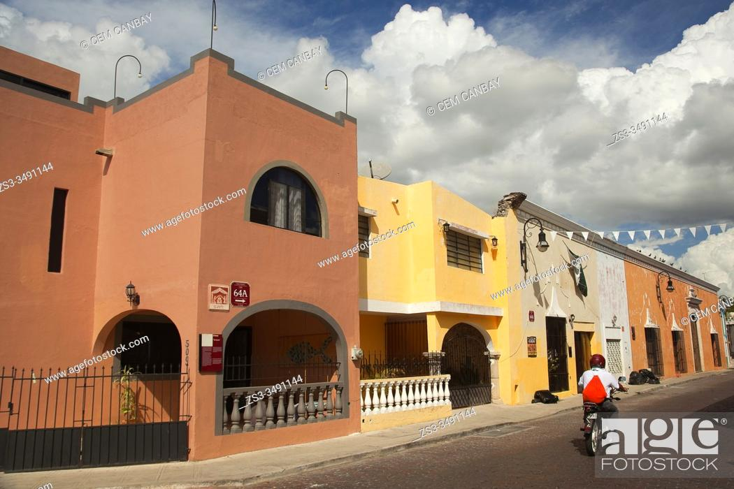 Stock Photo: Motoryclist at the street in front of the colonial buildings in the historic center, Merida, Yucatan State, Mexico, Central America.