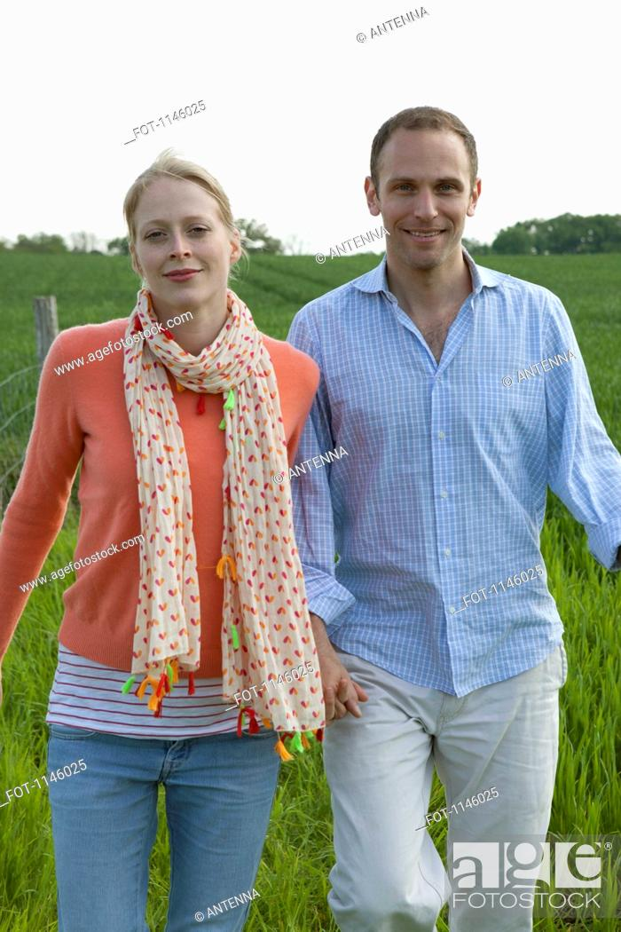 Stock Photo: A couple walking hand in hand in a field.
