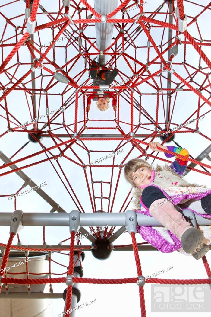 Stock Photo: Two kids looking down from jungle gym.