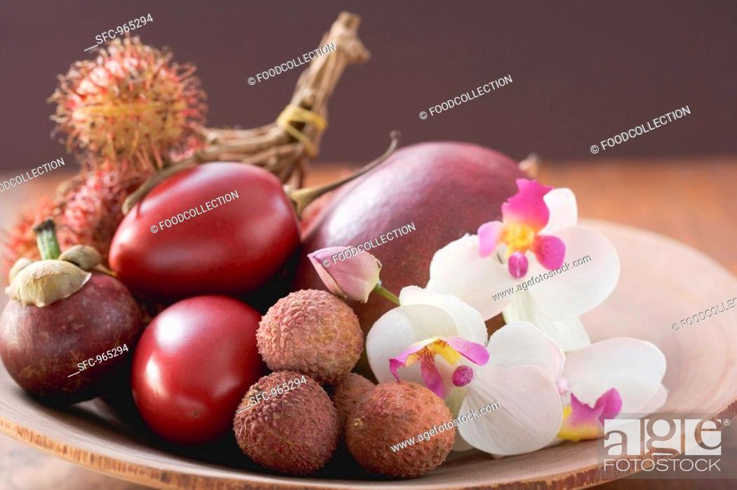 Stock Photo: Assorted exotic fruits in a dish with orchids.