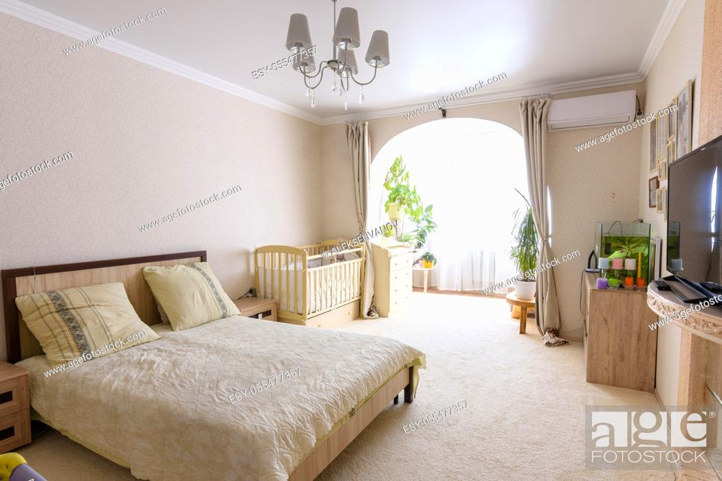 Stock Photo: Nice interior of a bedroom combined with a balcony and a crib for a newborn baby.