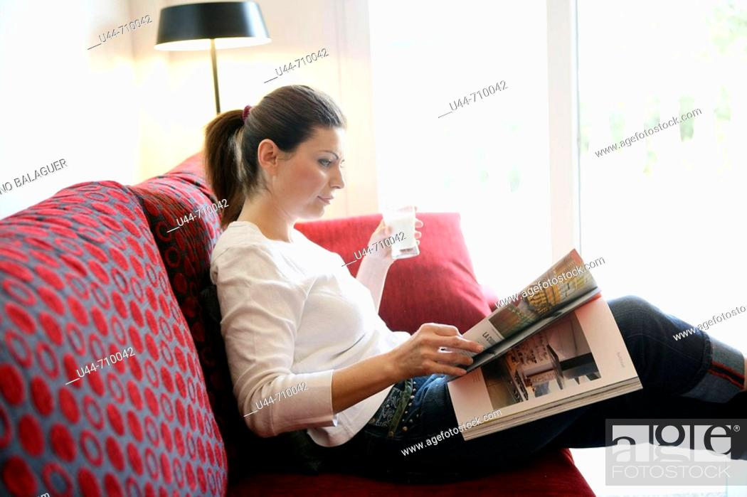 Stock Photo: Woman drinking a milk glass reading a book relaxed on the sofa.