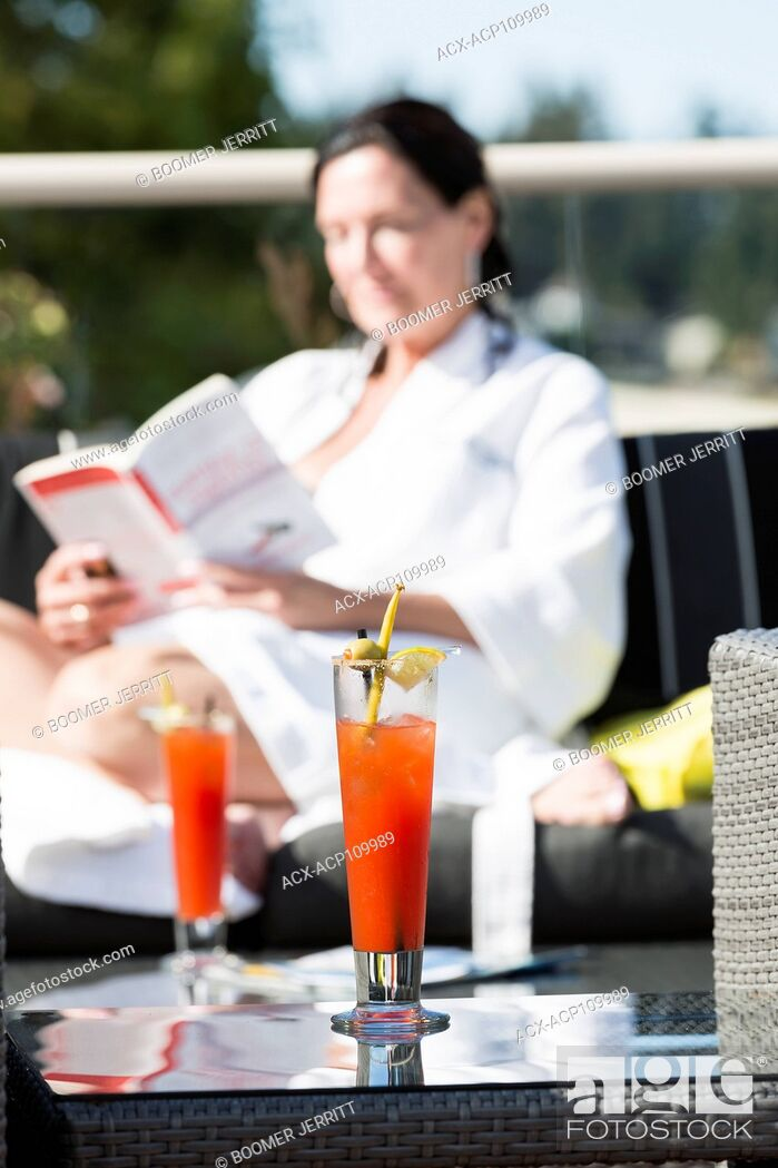 Stock Photo: A mature woman relaxes at the outdoor patio with a cocktail while visiting the Kingfisher Resort and spa. Courtenay, Vancouver Island, British Columbia, Canada.