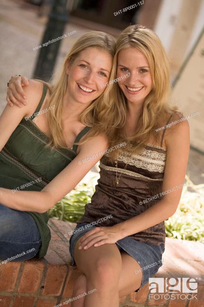 Stock Photo: Two women sitting on wall.