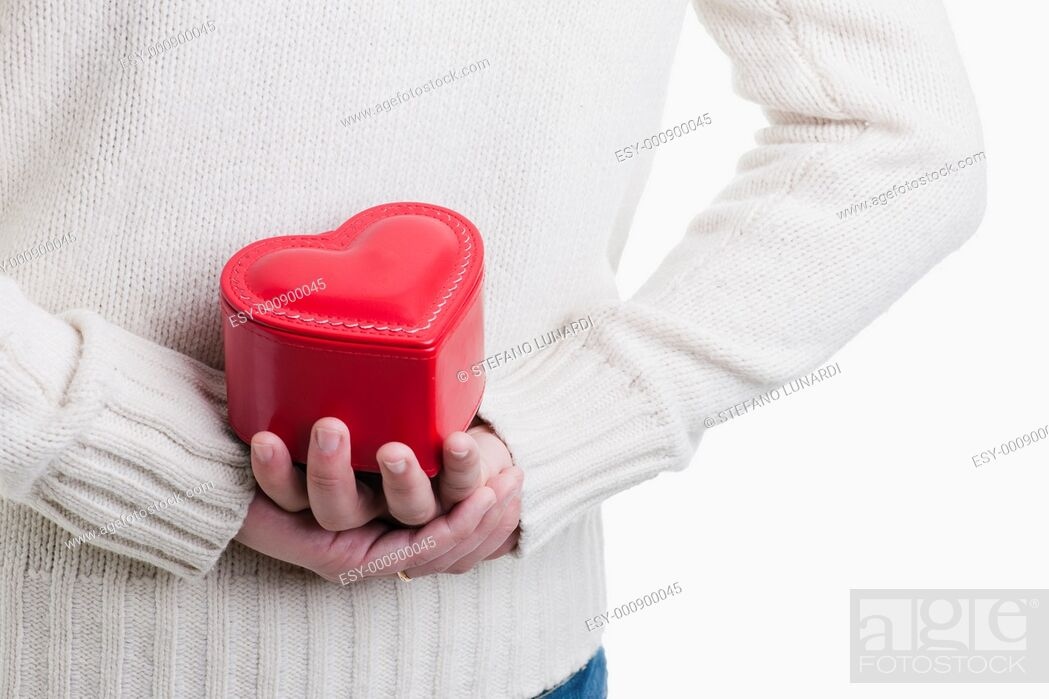 Stock Photo: Man hiding a heart shaped box, Valentine's day, Christmas or Anniversary.