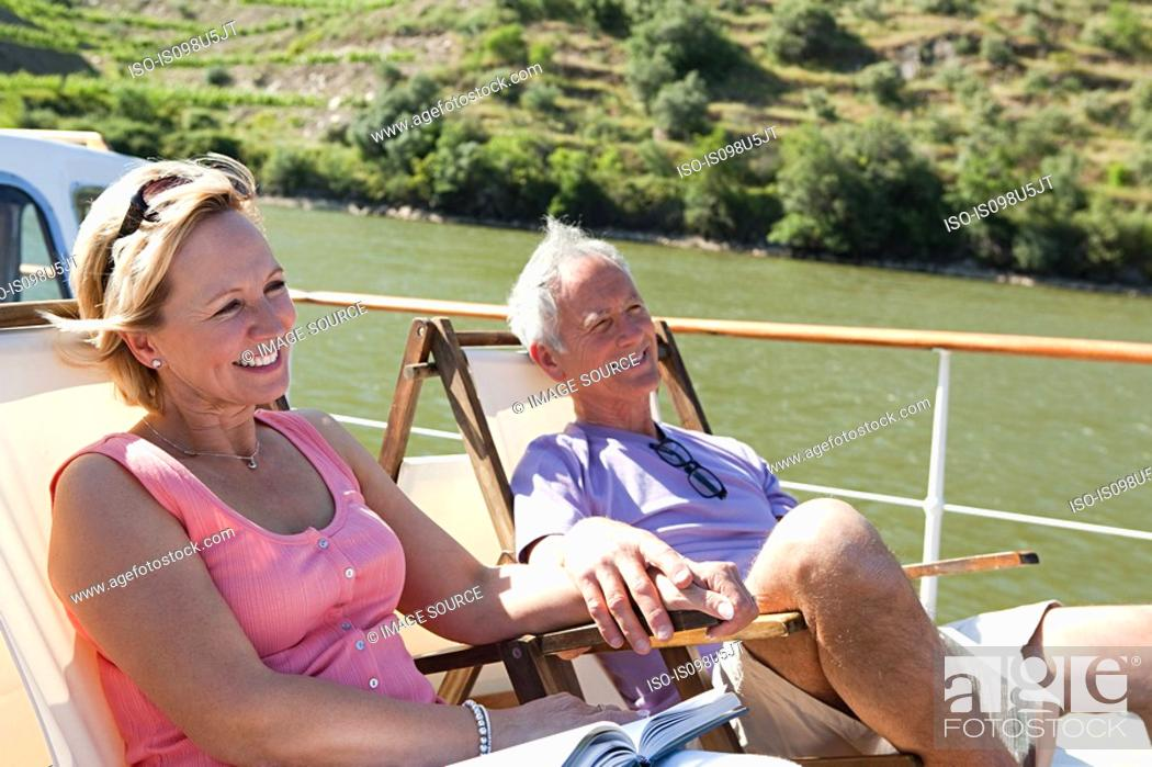 Stock Photo: Senior couple sitting on deckchairs on a boat.