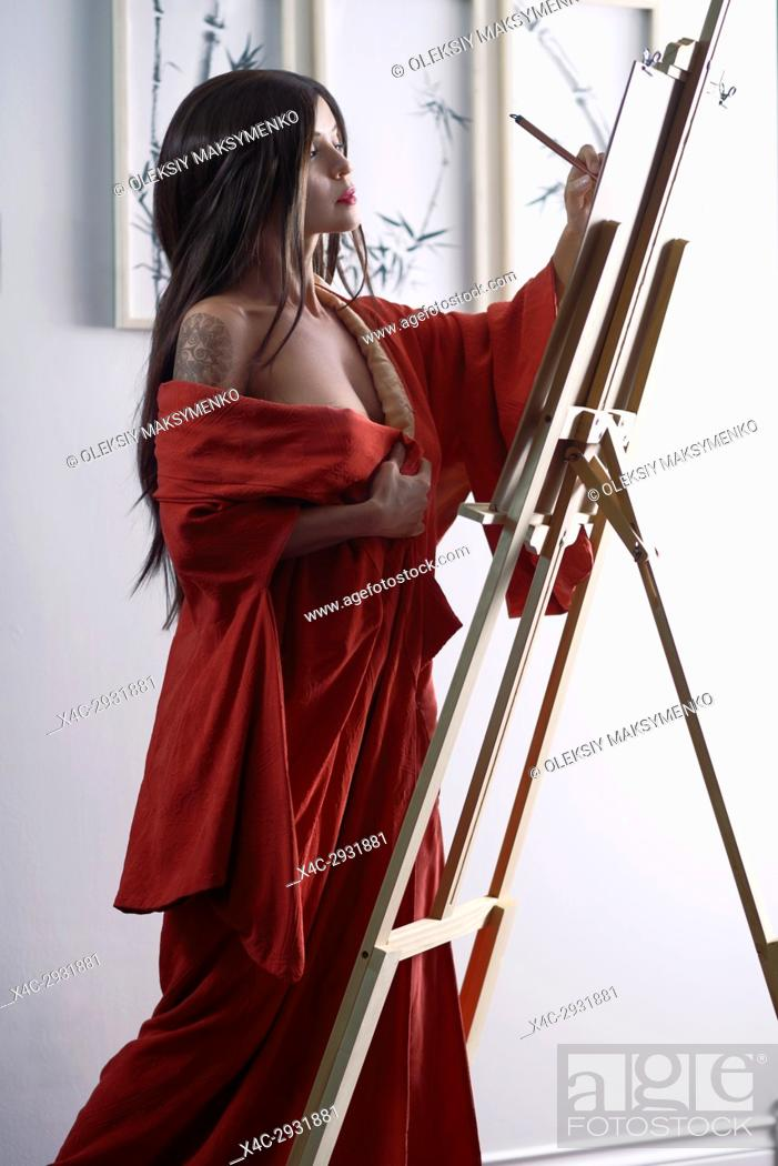 Stock Photo: Artistic sensual portrait of a beautiful asian woman in red kimono, Japanese sumi-e artist with an easel, painting in her studio.