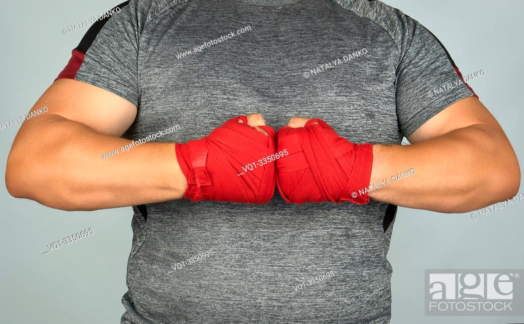Stock Photo: athlete in gray clothes joined his hands in front of his chest, two hands wrapped in a red textile sports bandage, white background.