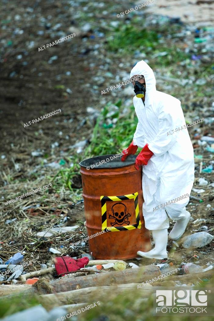 Stock Photo: Person in protective suit carrying barrel of hazardous waste.