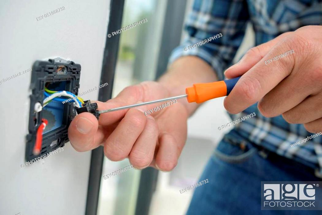 Stock Photo: Man connecting wires on dismantled switch.