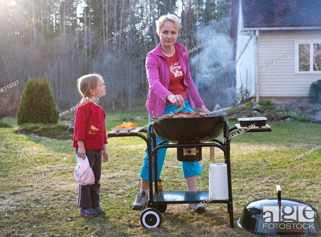 Stock Photo: Mother and Kid Girl Standing and Grilling at Barbeque Grill in Yard.