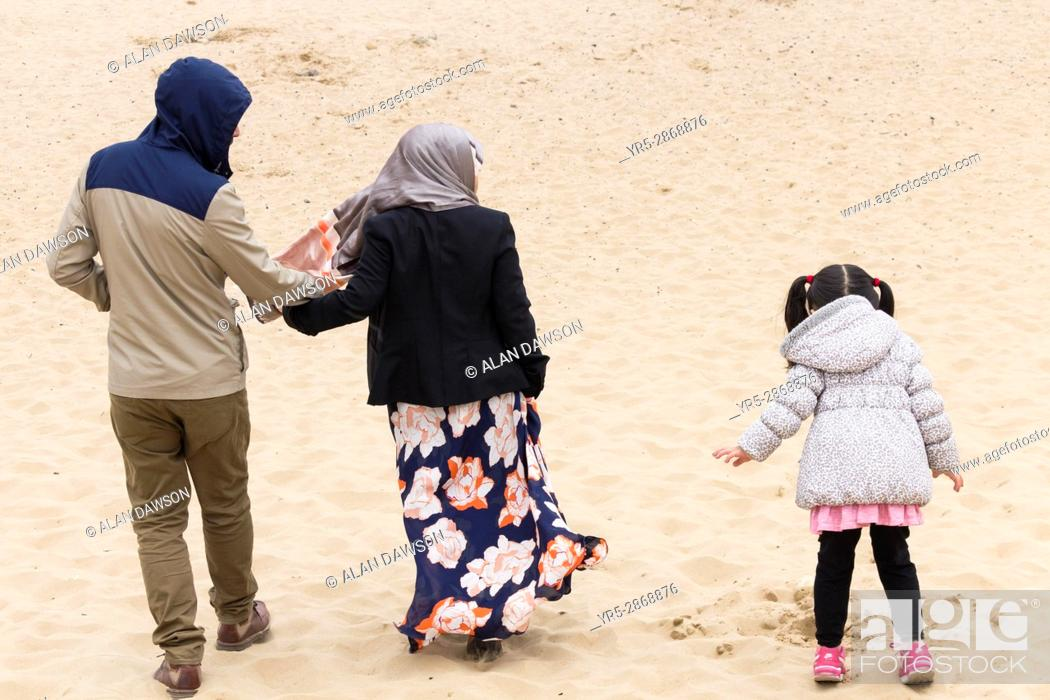 Stock Photo: Seaton Carew, County Durham, north east England. United Kingdom. Asian family on the beach on a cold overcast day.