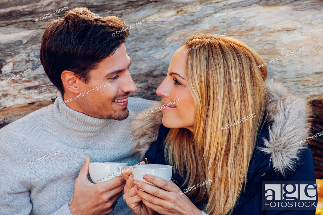 Stock Photo: Smiling couple holding cups outdoors smiling at each other.