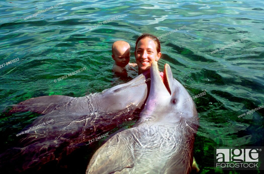 Stock Photo: Mother with children swimming with dolphins in Rancho Cangrejo, Varadero, Cuba. Rancho Cangrejo (that is the delfinario that is included in the Crucero del Sol).