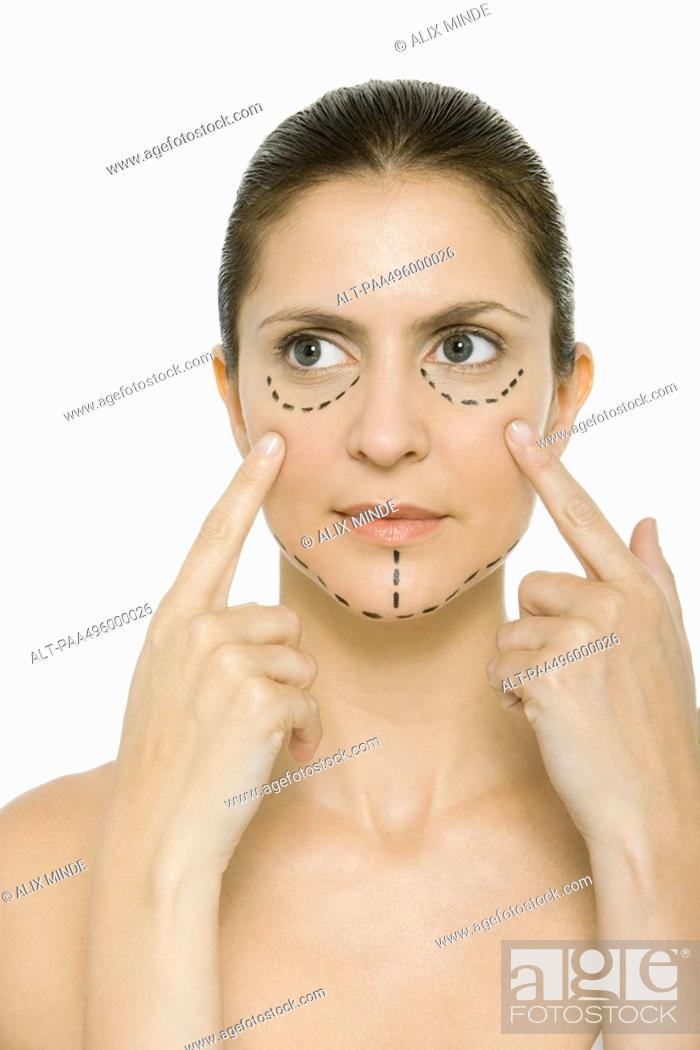 Stock Photo: Woman with plastic surgery markings on face, touching cheeks, looking away.
