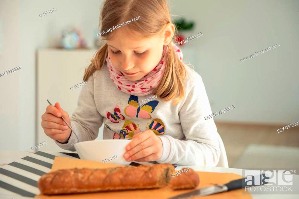 Stock Photo: Cute little girl eating soup with whole grain bread in bright living room at home.